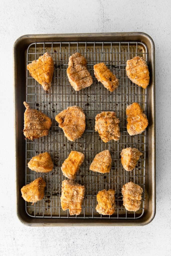 golden brown chicken nuggets on baking sheet